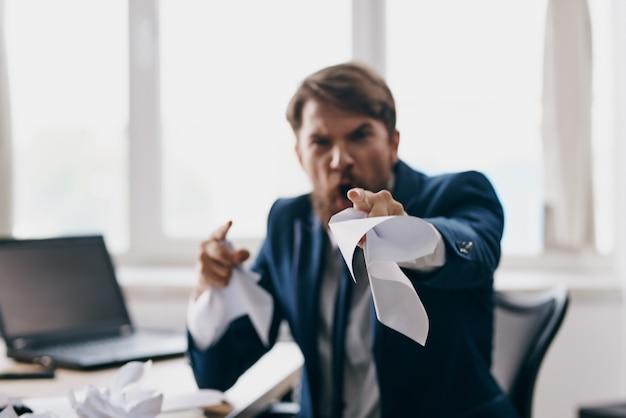 Biznesmeni siedzący przy biurku przed laptopem stresują profesjonalistę złości