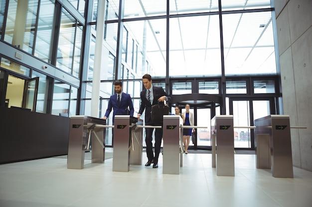 Biznesmeni skanują swoje karty przy bramce kołowrotu