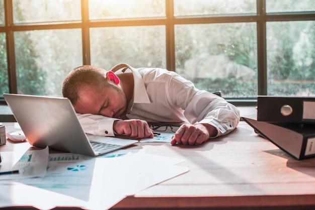 Biznesmeni śpią na biurku w biurze.