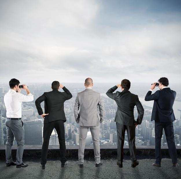 Biznesmeni spoglądają na miasto z dachu przez lornetkę