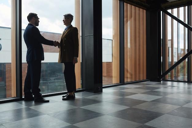 Biznesmeni spotykają się w biurowcu i ściskają ręce