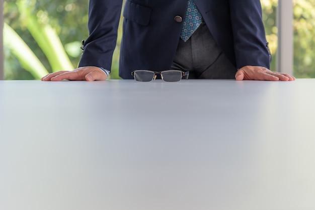 Biznesmeni stoi i stawia oba ręki i szkła stawia na konferencyjnym stole.