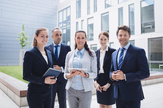 Biznesmeni stoi na zewnątrz budynku biurowego