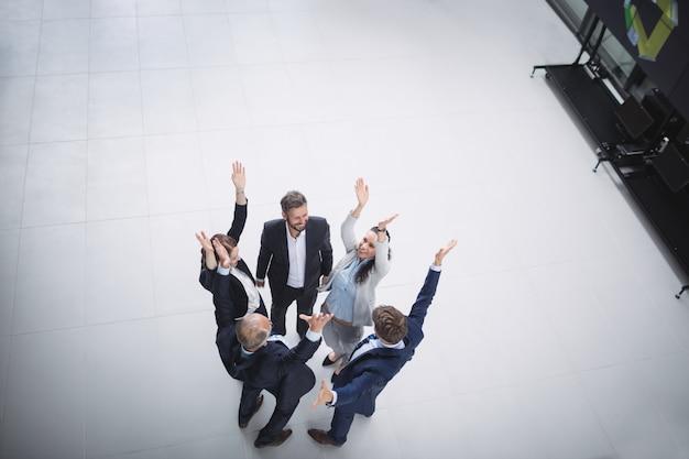 Biznesmeni stojąc z podniesionymi rękami
