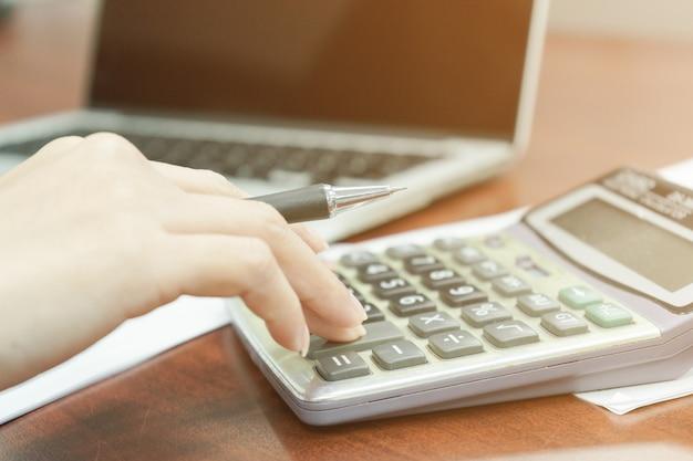Biznesmeni trzyma pióra używać kalkulatory i komputery