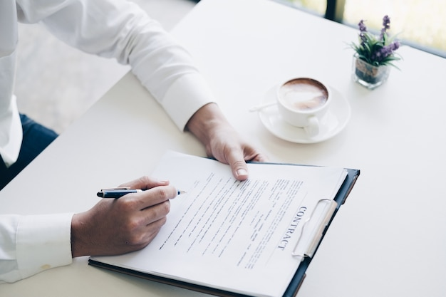 Biznesmeni trzyma pióro pisać biznesowego dokument i kontraktu prześcieradło