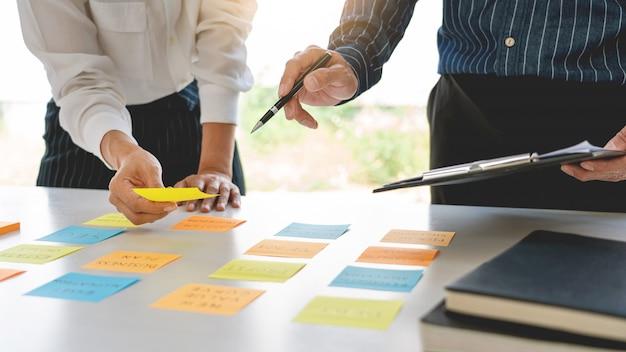 Biznesmeni układają notatki z kolegami i przeprowadzają burze mózgów na temat priorytetów pracy kolegi w nowoczesnej przestrzeni coworkingowej.