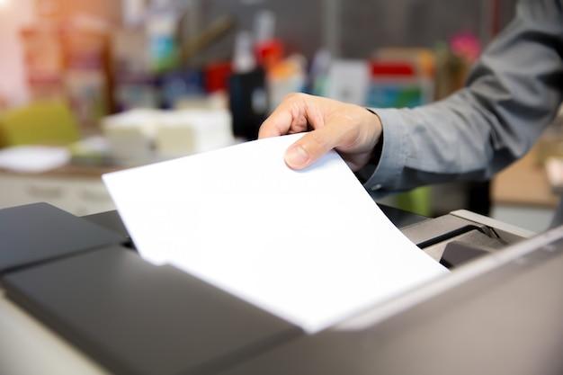 Biznesmeni umieszczają papiery na kserokopiarkach.