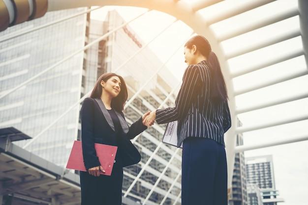 Biznesmeni uzgadniają się z współpracownikiem, handel partnerem handhake współpracują razem.