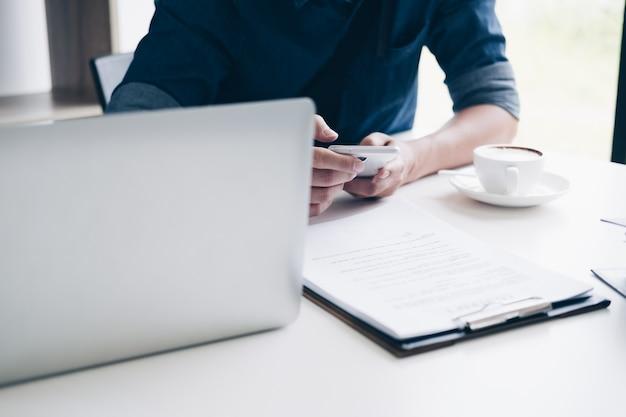 Biznesmeni używa smartphone podczas gdy siedzący przy biurkiem z laptopem, papierkową robotą i filiżanką