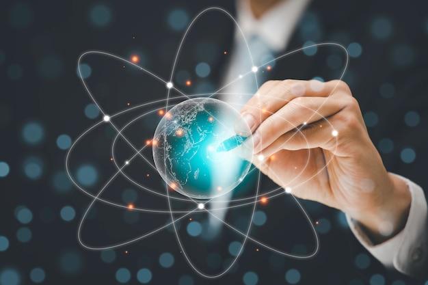 Biznesmeni używają długopisu do powiększania atomu