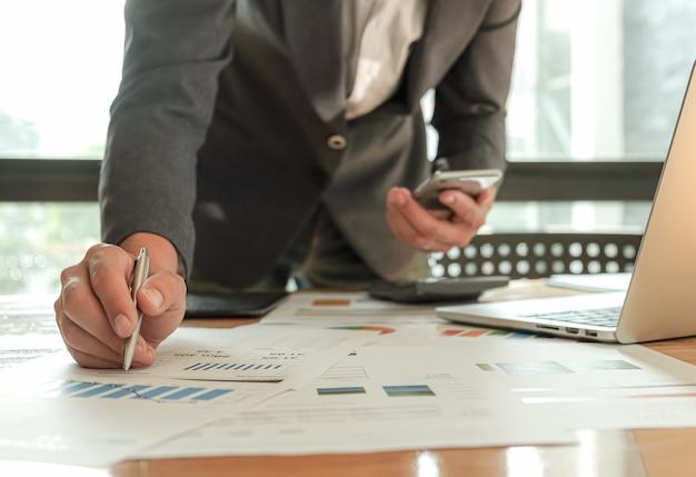 Biznesmeni używają długopisu, laptopa i telefonu komórkowego, planują marketingowy plan poprawy jakości pracy.