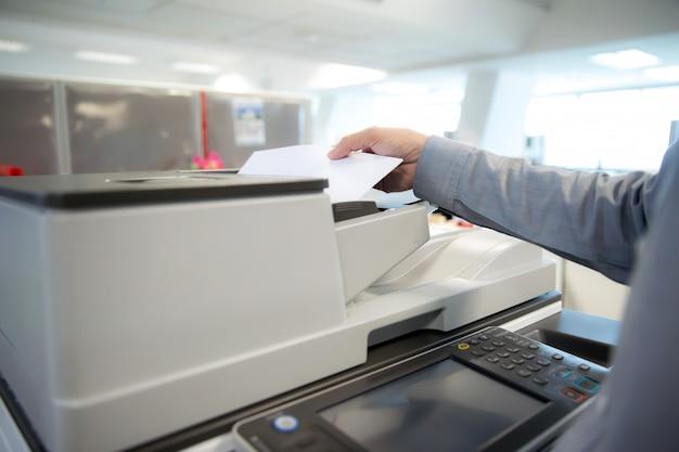 Biznesmeni używają kserokopiarek, skanera.