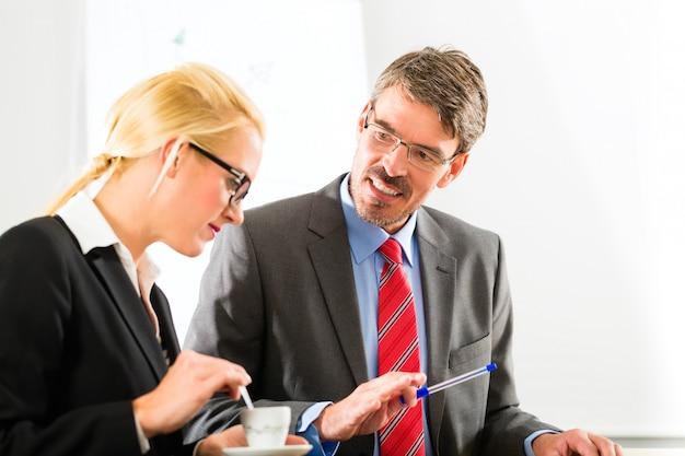 Biznesmeni w biurze firmy piją kawę