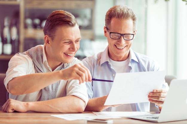 Biznesmeni w codziennych ubraniach studiują dokument.