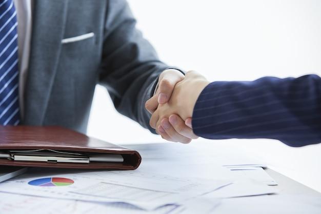 Biznesmeni w eleganckich garniturach na spotkaniu biznesowym ściskają sobie ręce w biurze