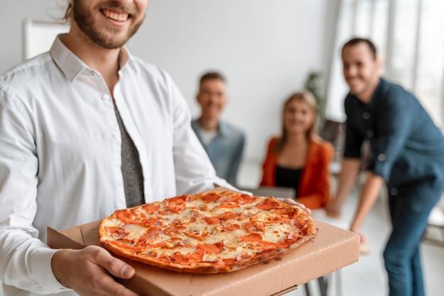 Biznesmeni w przerwie obiadowej jedzą pizzę