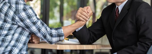 Biznesmeni walczą na rękach razem, konkurencja biznesowa.