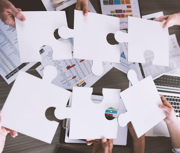 Biznesmeni współpracujący przy tworzeniu puzzli