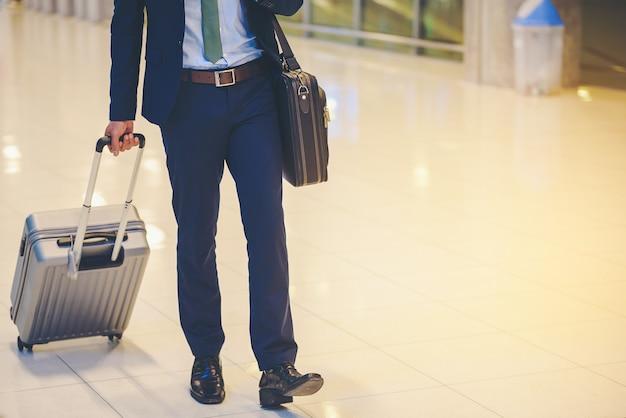 Biznesmeni wyjeżdżają z bagażem na lotnisku.