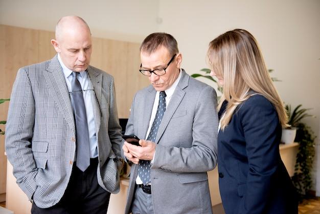 Biznesmeni wysyłają wiadomości tekstowe lub wysyłają wiadomości za pomocą telefonu komórkowego