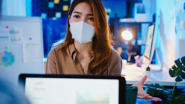 Biznesmeni z azji korzystający z pomysłów na prezentację laptopa i komunikację podczas burzy mózgów