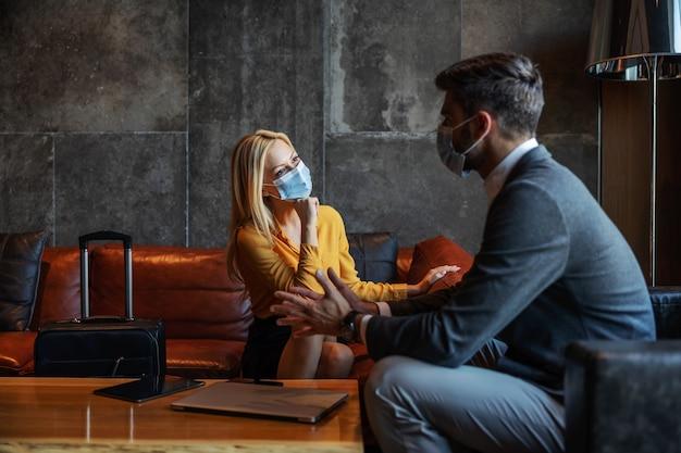 Biznesmeni z maskami na twarz siedzący w hotelowym lobby i rozmawiający podczas pandemii koronawirusa