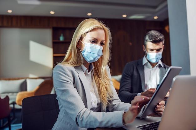 Biznesmeni z maskami na twarz siedzi w kawiarni i po spotkaniu biznesowym. kobieta za pomocą tabletu. spotkanie zoom, technologia, telekomunikacja podczas covid-19, koronawirus