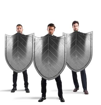 Biznesmeni z tarczami. koncepcja ochrony i obrony w świecie biznesu