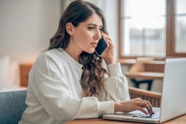 Biznesmenka. przystojna młoda kobieta w białej bluzce pracuje na laptopie i rozmawia przez telefon