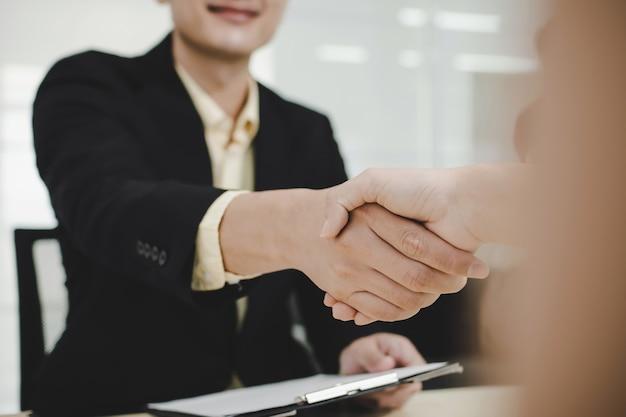 Biznesmenów partner uścisk dłoni po podpisaniu umowy biznesowej biurko w sali konferencyjnej