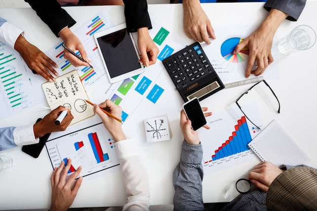 Biznesmenów ręce na białym stole z dokumentami i szkicami