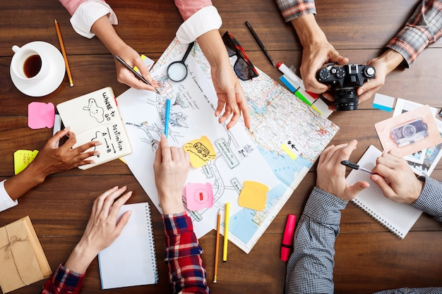 Biznesmenów ręce na drewnianym stole z dokumentami i szkicami