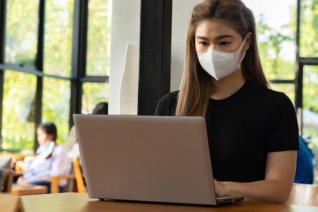 Biznesowa azjatycka młoda kobieta pracuje z komputerowym laptopem i jest ubranym maskę ochronną przeciąża się infekcją wirusową