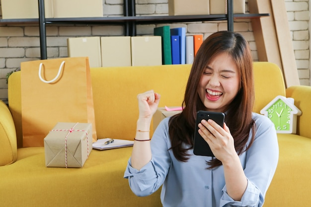Biznesowa azjatykcia kobieta jest szczęśliwa z jej online rozkazem w smartphone.