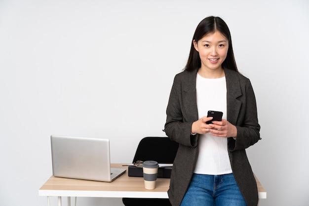Biznesowa azjatykcia kobieta w jej miejscu pracy na biel ścianie wysyła wiadomość z telefonem komórkowym