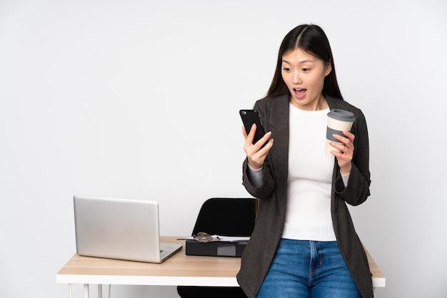 Biznesowa azjatykcia kobieta w jej miejscu pracy na biel ściany mienia kawie brać daleko od i wiszącej ozdobie
