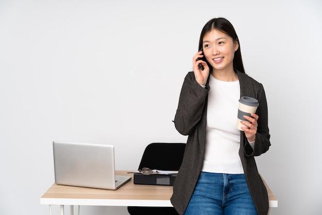 Biznesowa azjatykcia kobieta w jej miejscu pracy na biel ściany mienia kawie zabierać i wisząca ozdoba