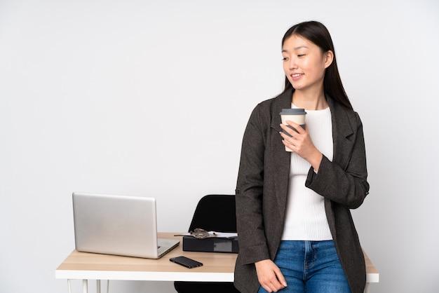 Biznesowa azjatykcia kobieta w jej miejscu pracy na biel ściany przyglądającej stronie