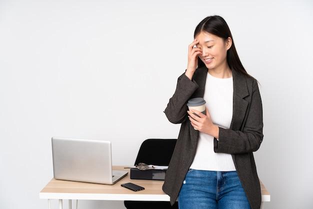 Biznesowa azjatykcia kobieta w jej miejscu pracy na biel ściany śmiać się