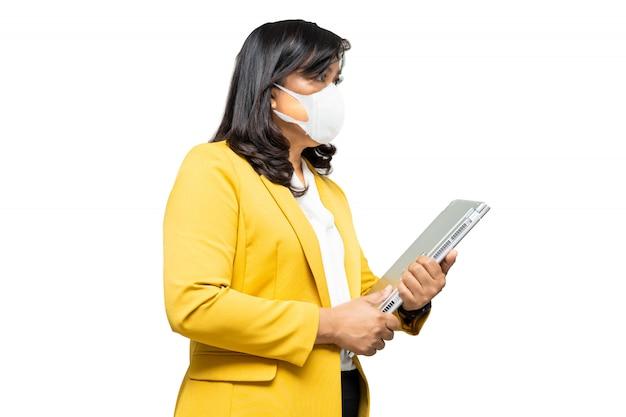 Biznesowa dama azjatyckich noszenie maski i trzymanie laptopa