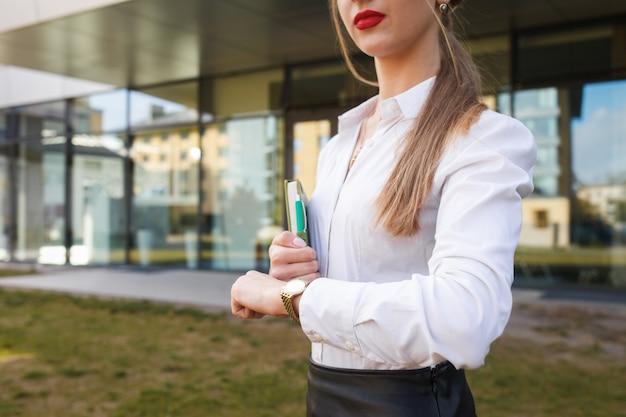 Biznesowa dama patrzy na zegarek. młoda dziewczyna spieszy się na spotkanie