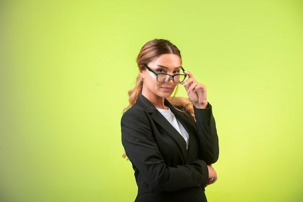 Biznesowa dama w czarnej marynarce i okularach wygląda pewnie.