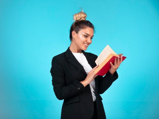 Biznesowa dama w czarnej marynarce z czerwoną książką i czyta.