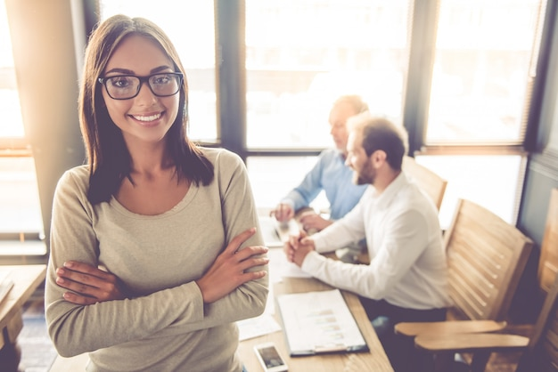 Biznesowa dama w eyeglasses jest przyglądającym kamerą i ono uśmiecha się