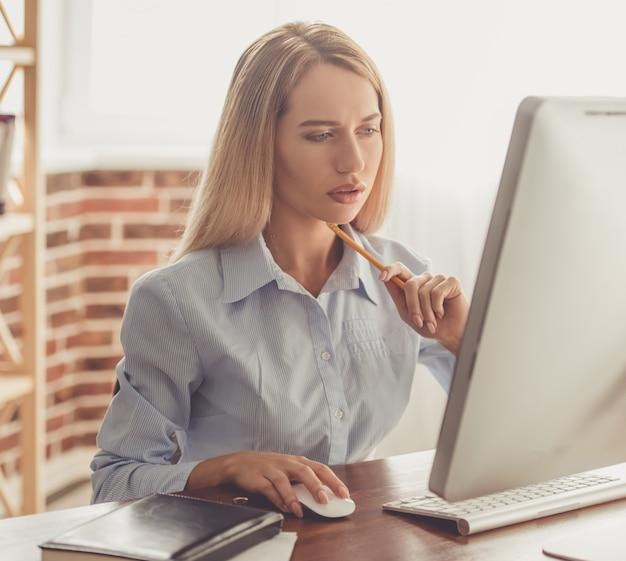 Biznesowa dama w formalnej koszula używa komputer