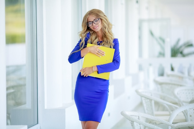 Biznesowa dama z żółtą falcówką i telefonem.