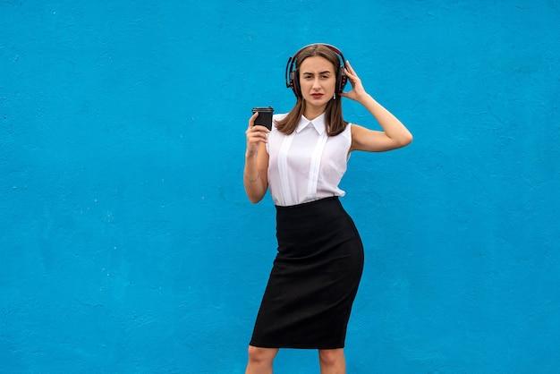 Biznesowa dama zatrzymuje się w pracy, pijąc kawę i słuchając muzyki odizolowanej na niebiesko
