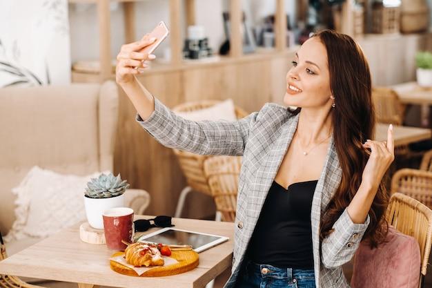 Biznesowa dziewczyna siedzi w kawiarni i robi selfie