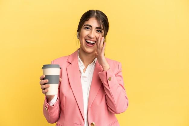 Biznesowa kaukaska kobieta na żółtym tle krzyczy z szeroko otwartymi ustami